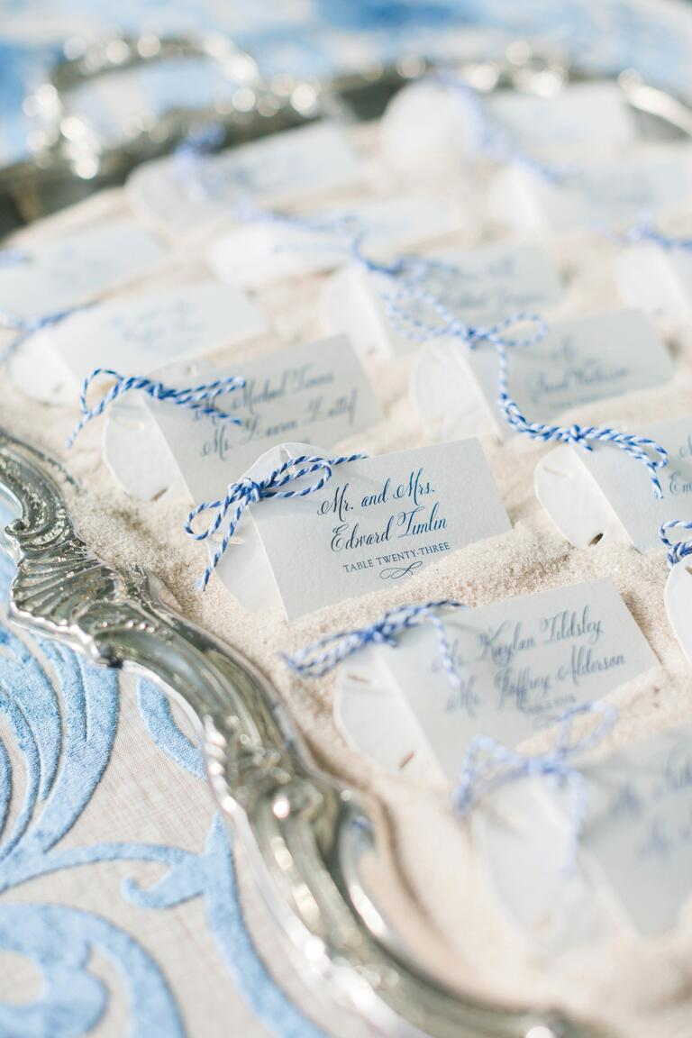White and Blue Escort Cards on Silver Platter With Sand and Striped Twine