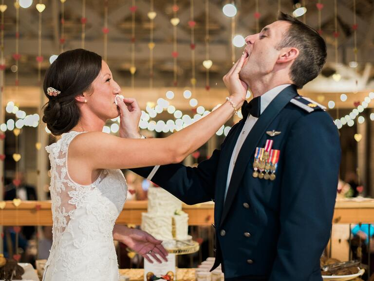 Bride and groom smashing cake into each other's faces