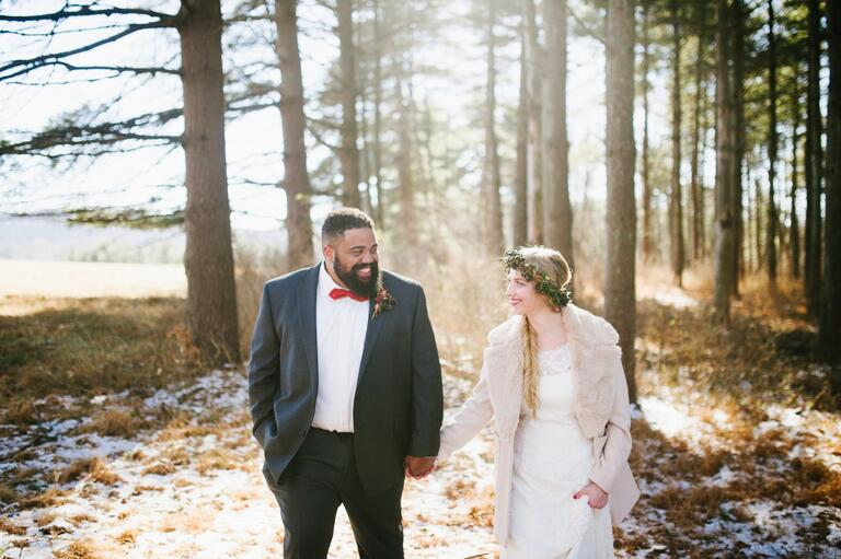 Couple holding hands at their bohemian winter wedding