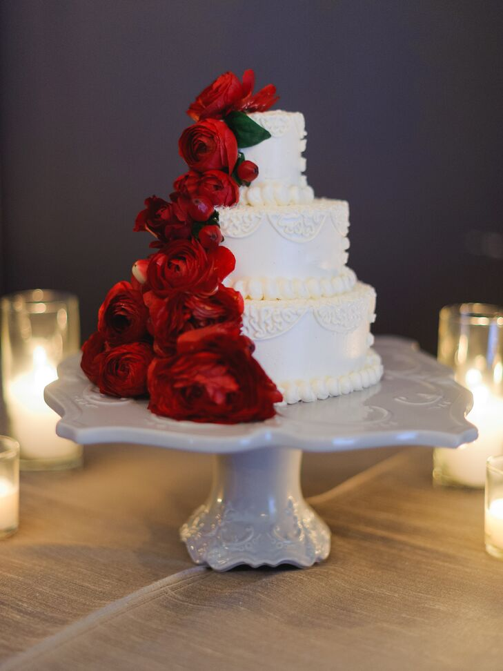 The three-tiered ivory wedding cake was adorned with red ranunculus flowers going down the side from top to bottom. The cake was displayed on an elegant stand.