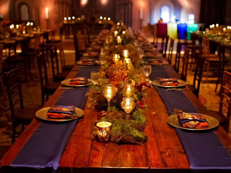 Long wood tables are set with purple runners and candles