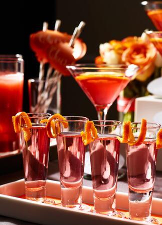 Colorful signature cocktails with orange garnish | David Prince | blog.theknot.com