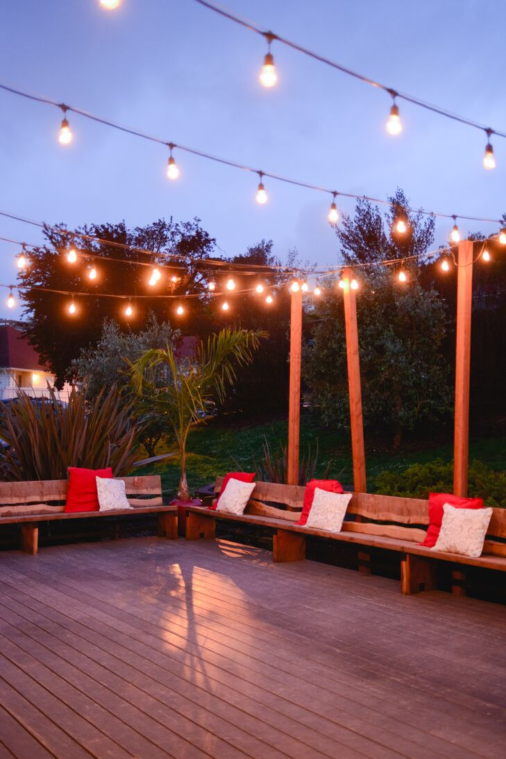 The back deck was decorated with wood benches with white and red pillows and string lights.rn