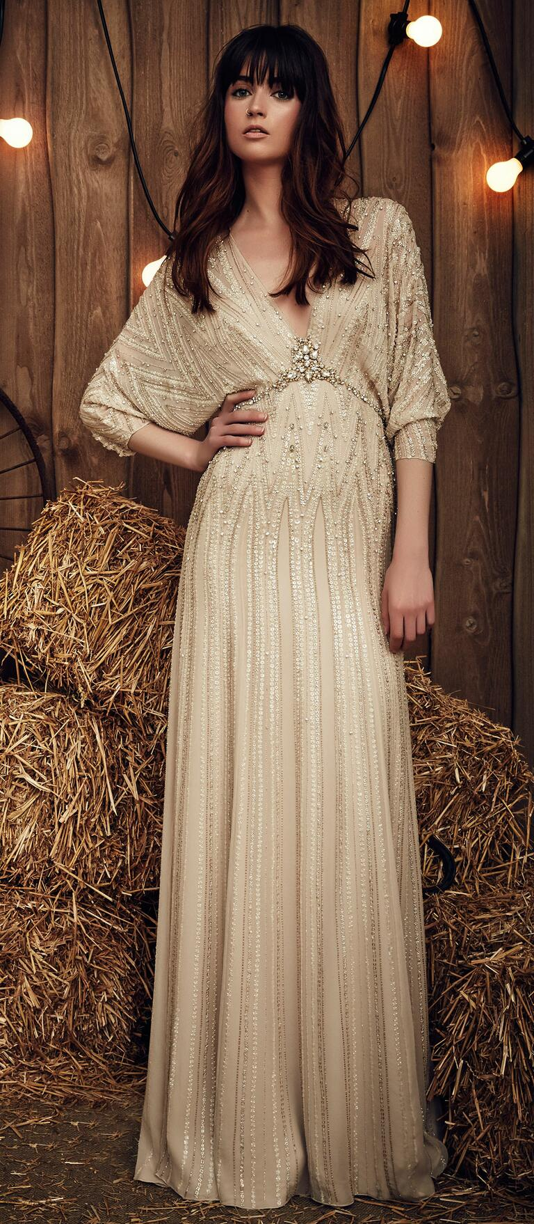 Jenny Packham Spring 2017 Montana wedding dress in a barley hue with a gypsy-inspired, drop-wait silhouette, gathered three-quarter-length sleeves, and intricate stone and sequin embellishment from the waist to the plunging neck line