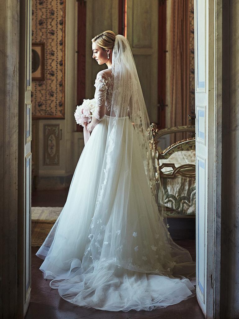 bride wearing a long veil with floral applique