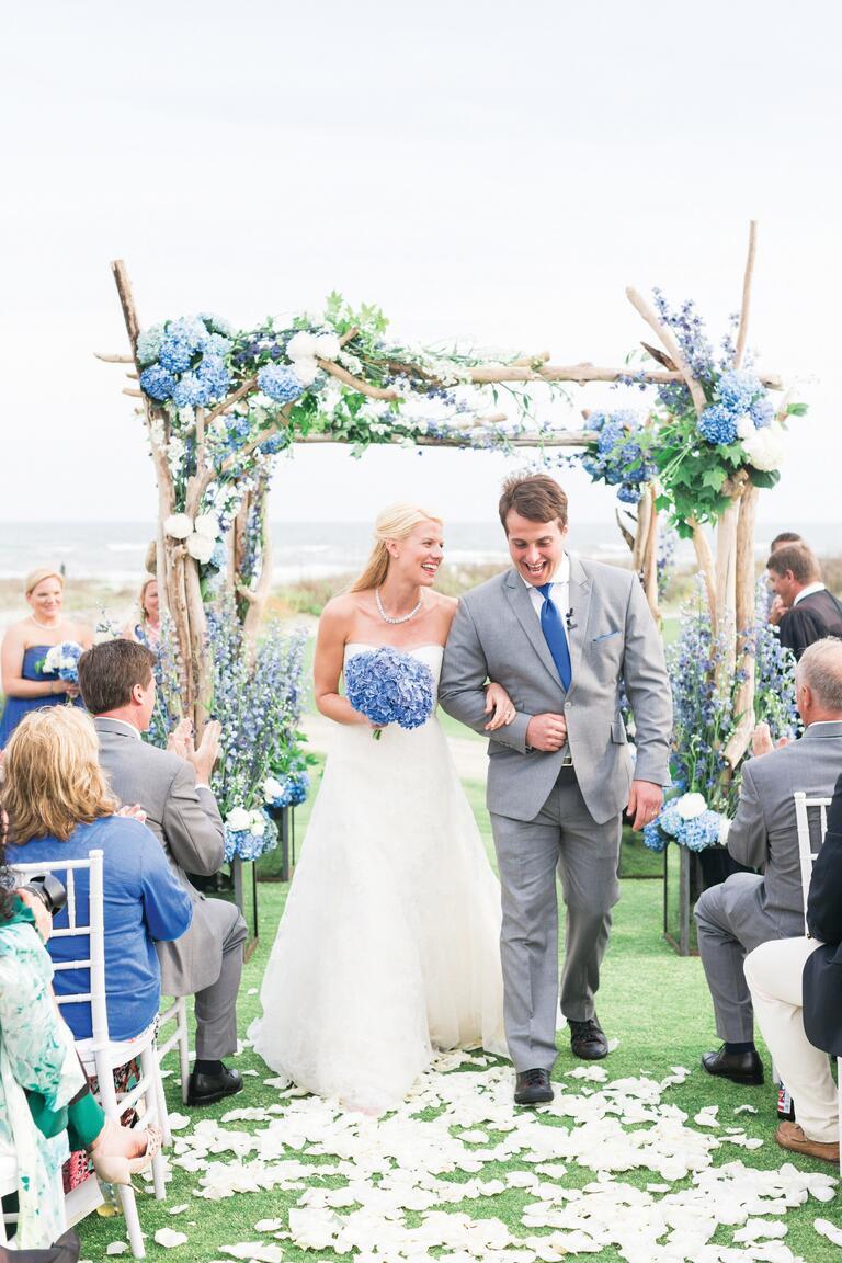 Bride And Groom Walking Down Petal Aisle In Outdoor Wedding