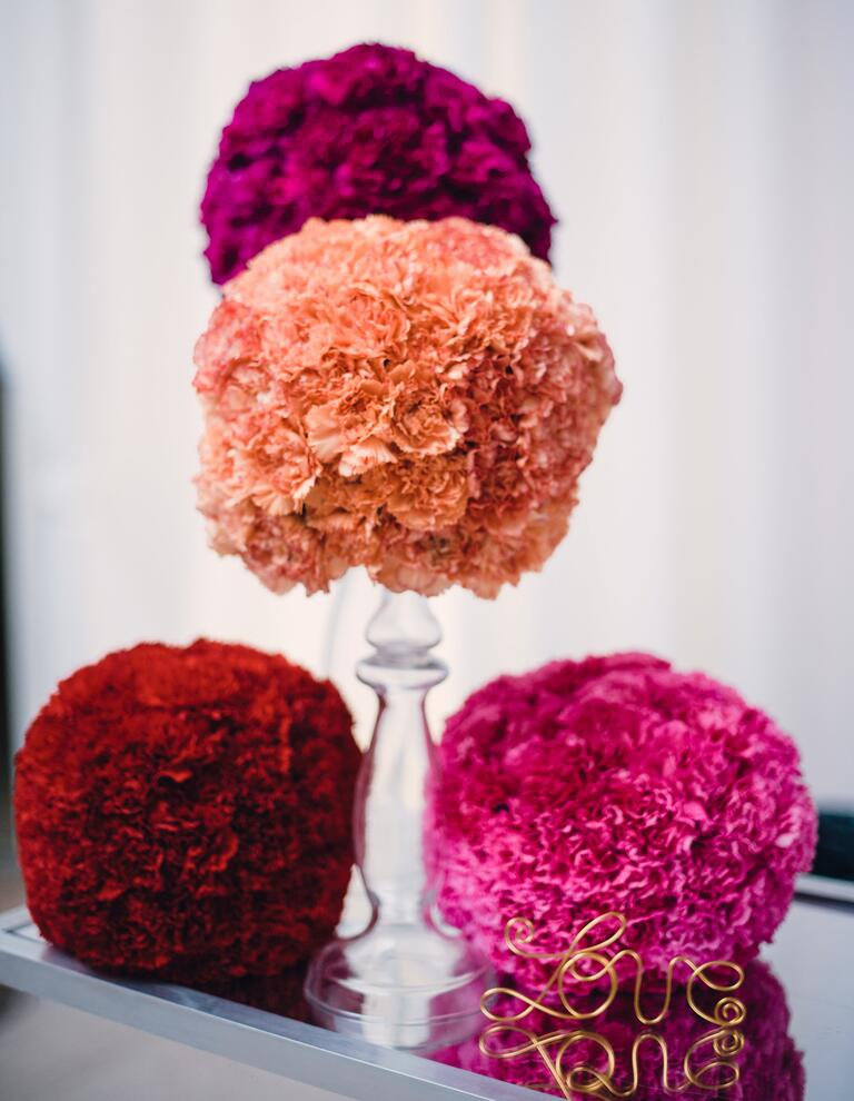 Orange, pink, and red carnation pomander wedding decor