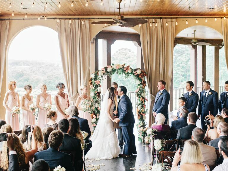 indoor summer wedding ceremony with string lights and garland wedding