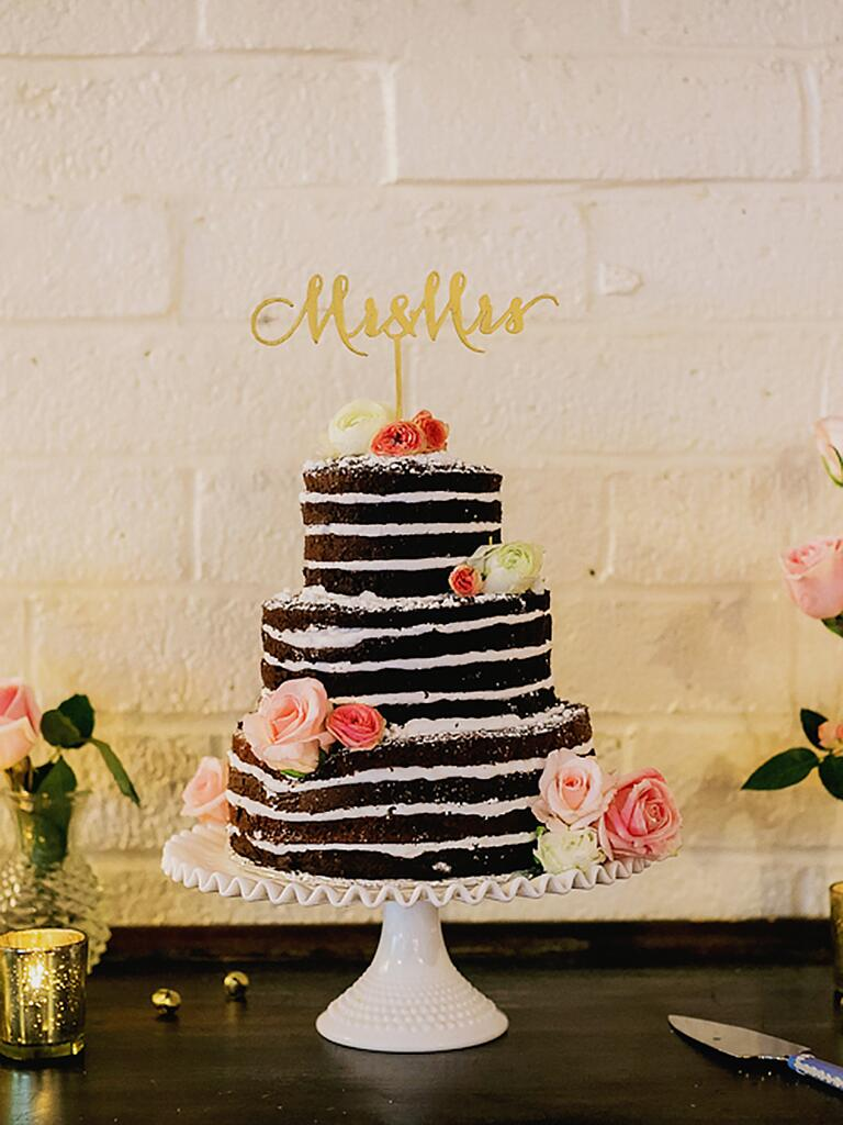 Naked chocolate wedding cake with vanilla frosting and fresh roses
