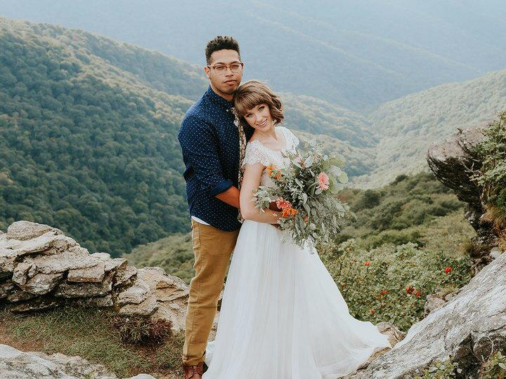 Bride and groom pose on a mountainside