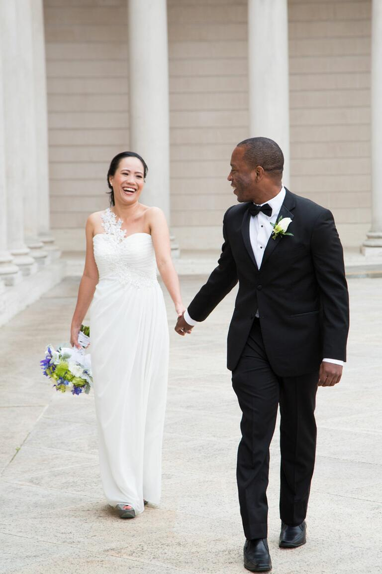Bride in one-shoulder wedding gown and groom in classic black tux