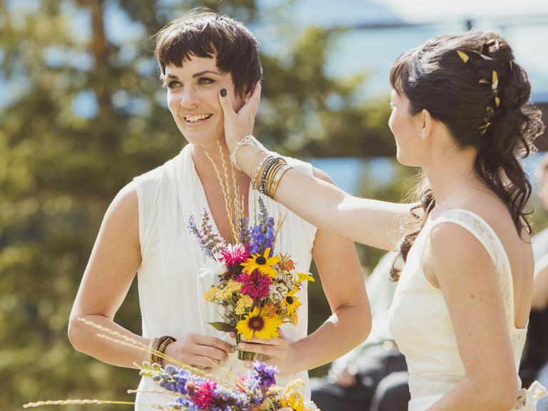 Brides hand on face with wildflowers outdoor ceremony -- same-sex wedding