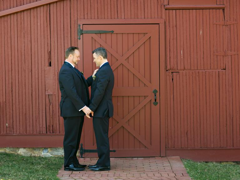 Grooms standing at barn