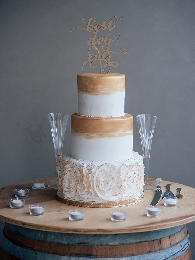 Three tier white wedding cake with gold detailing