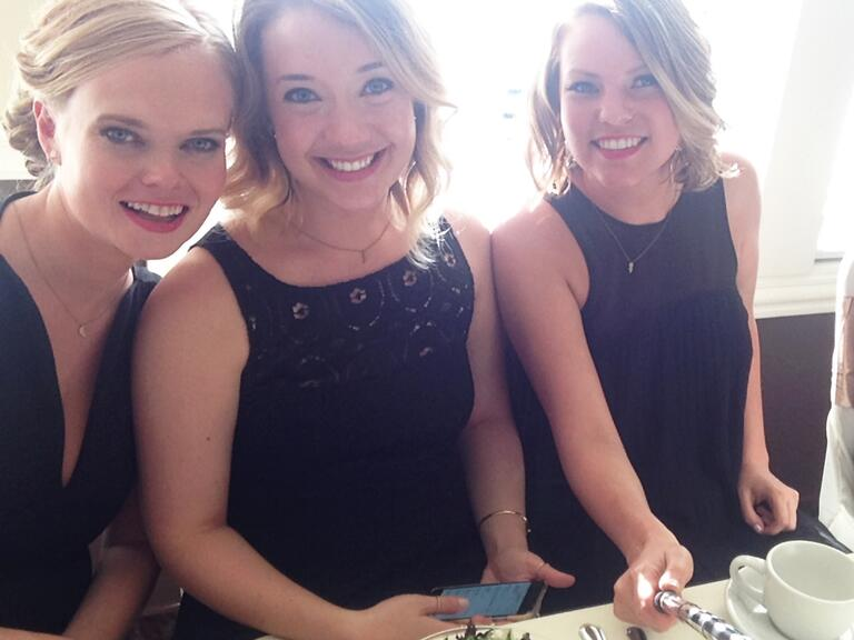 Bridesmaids at the reception table wearing black dresses, taking a picture with selfie sticks