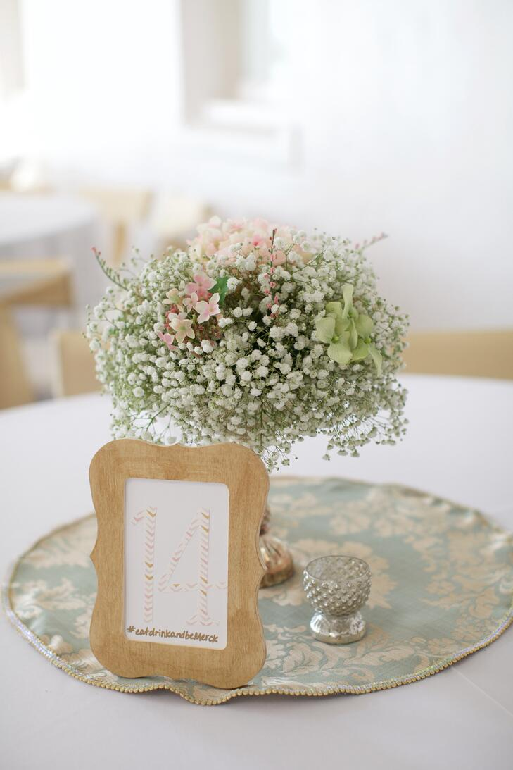 Baby's breath centerpieces with table numbers in wooden frames and wedding hashtag