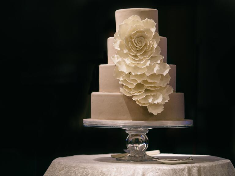 Greige wedding cake with a cascading white blossom