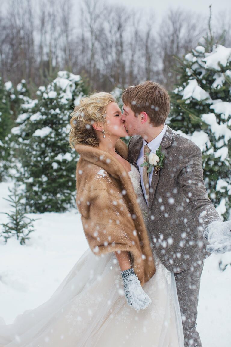 Bride in a fur stole kissing groom