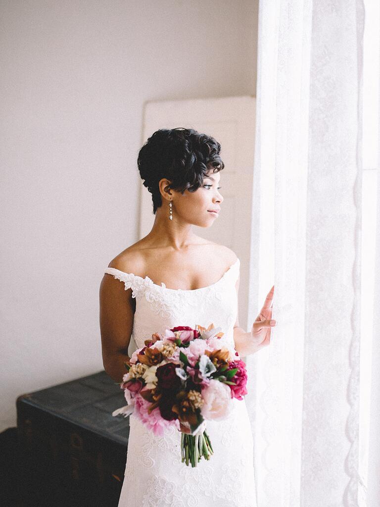 bride wearing off-the-shoulder dress holding a romantic bouquet