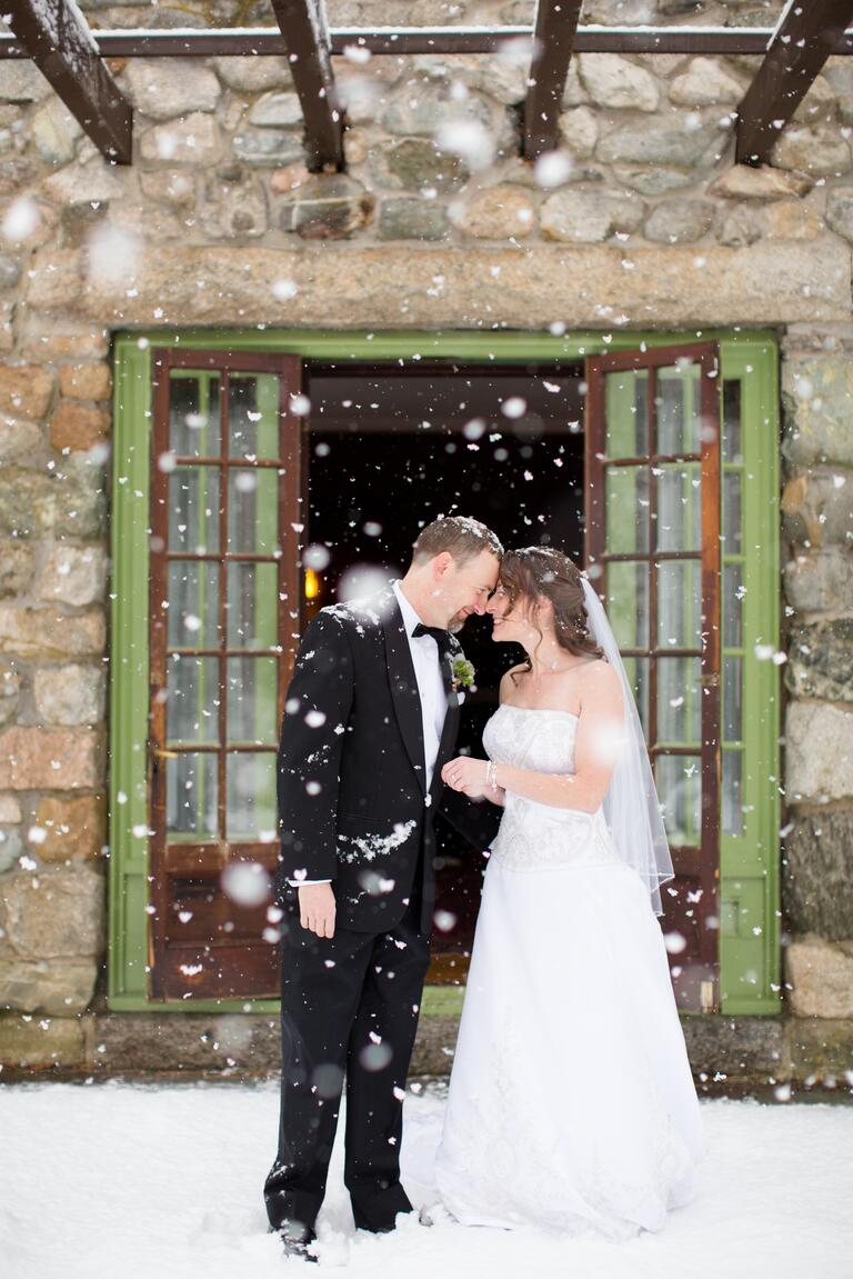 Couple looking at each other in the snow at their winter wedding