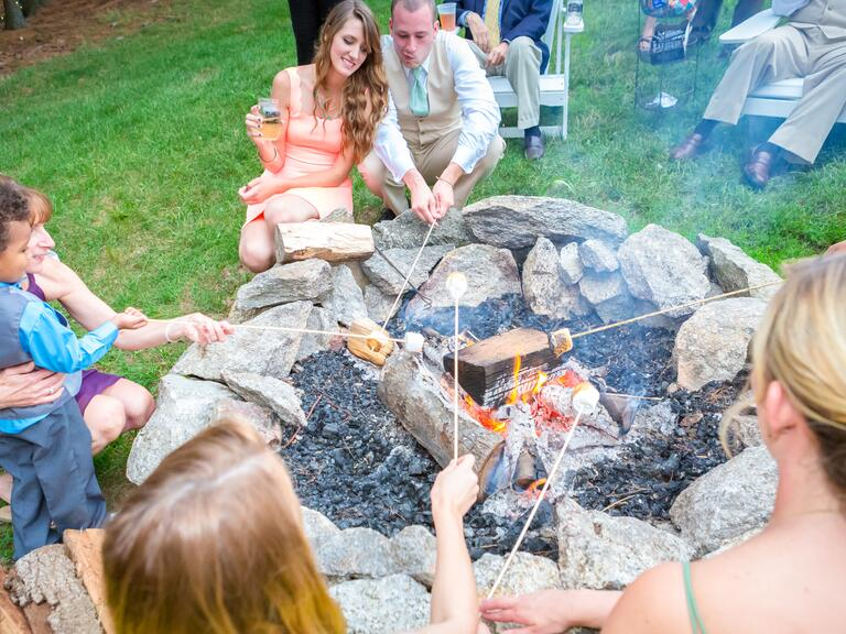 Reception bonfire with guests roasting s'mores