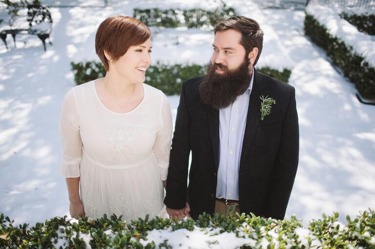 Bride in a long-sleeve gown and groom wearing a rosemary and herb boutonniere