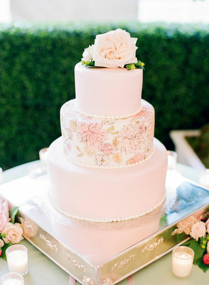 Blush pink wedding cake with painted floral details