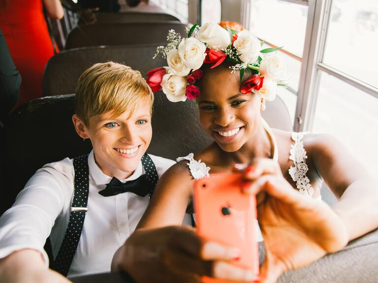Brides taking a selfie on the bus - same-sex wedding