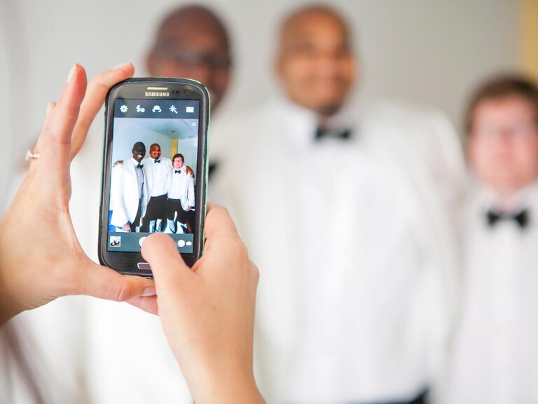 Person taking a photo of three groomsmen with their phone