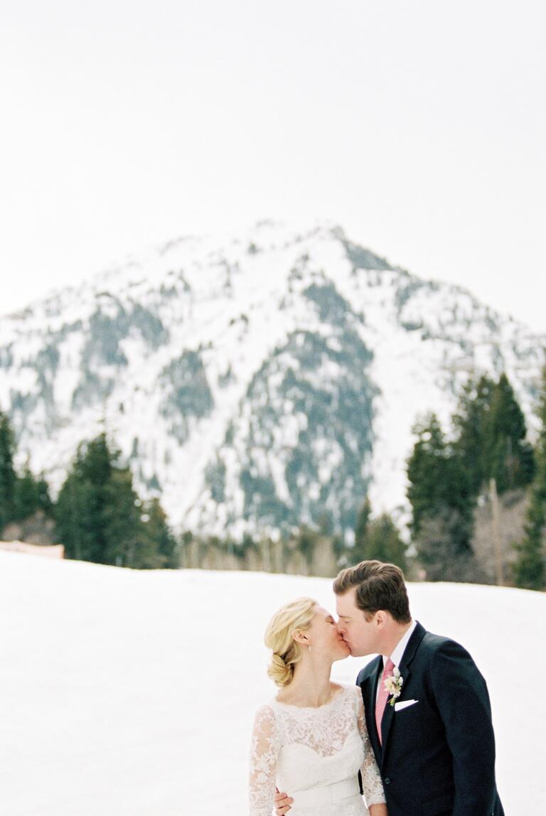 Couple kissing with snowy mountains in background