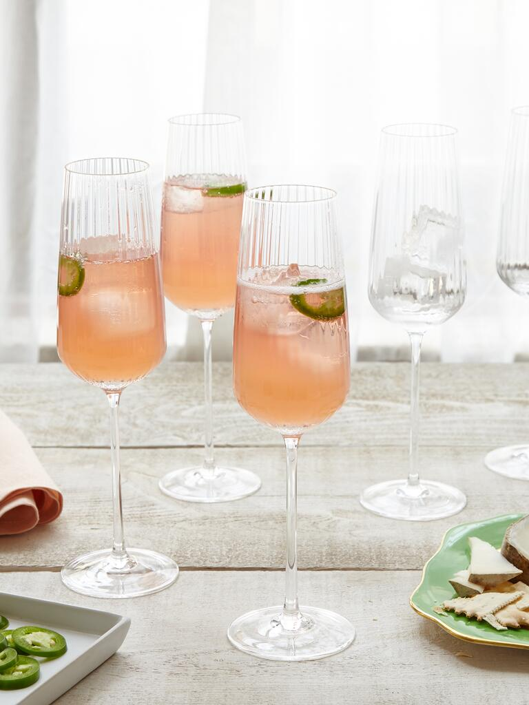 Pink chandy cocktail with jalapenos in champagne flutes