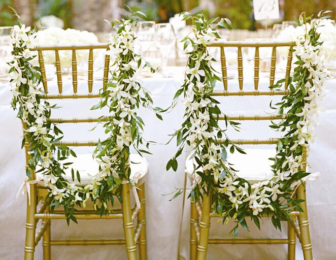 Leafy garlands for bride and groom chairs at wedding reception