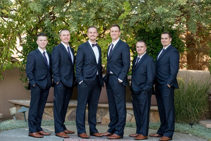 Brett wore a dark blue tux without the vest, as did the rest of the groomsmen. Brett stood out by donning a dark purple bow tie, while the groomsmen wore regular dark purple ties.
