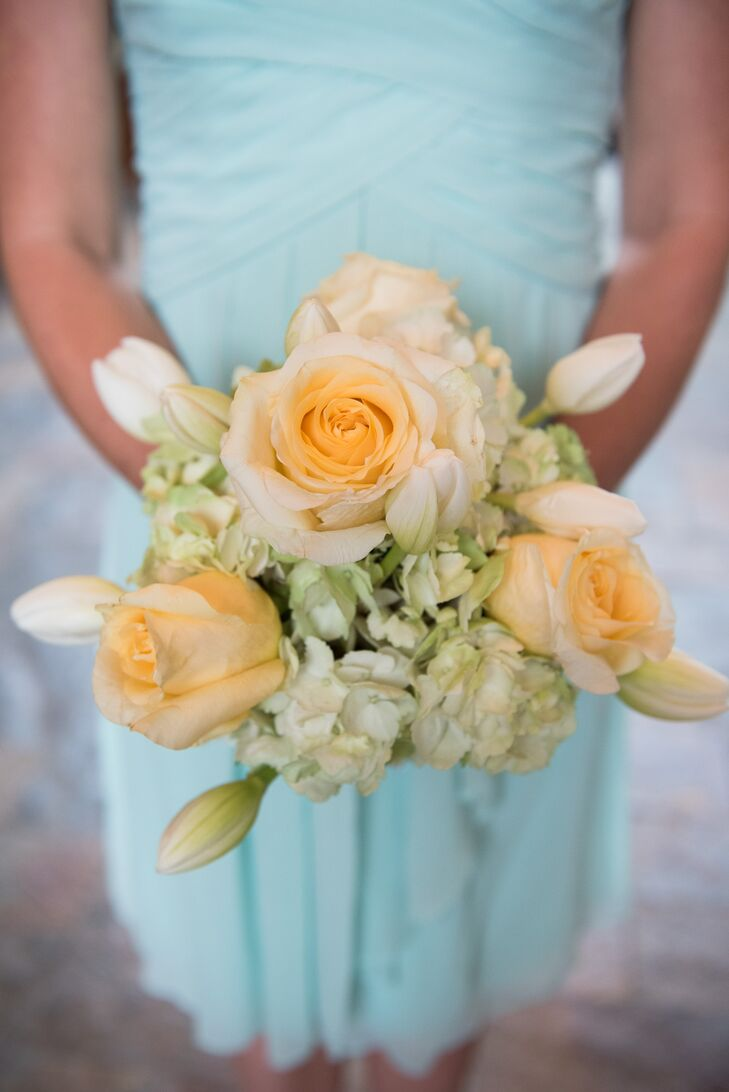 The bridesmaids carried soft, romantic bouquets filled with pale yellow roses, pale green hydrangeas, and white tulips.