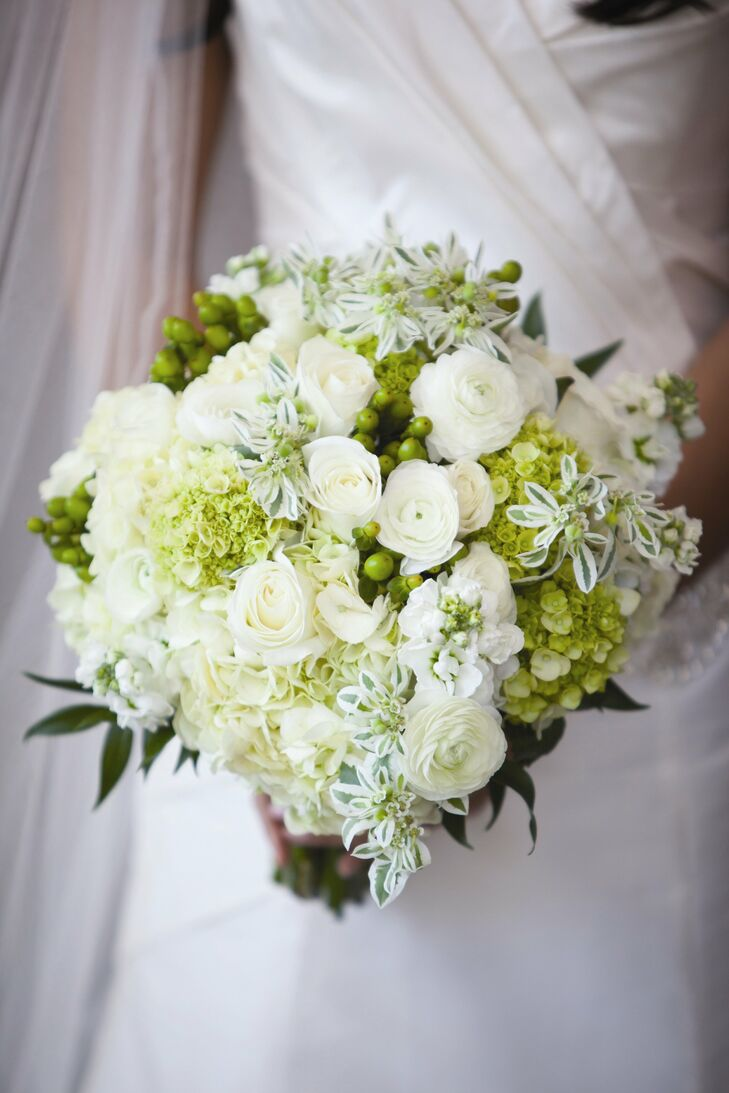 Tessa carried a lush, green and white bouquet filled with roses, ranunculuses, stock, hypericum berries and hydrangeas.