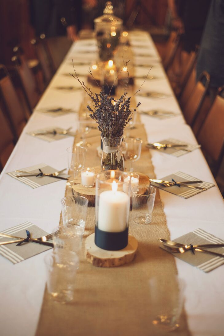"At the reception, dining tables were draped with burlap runners and decorated with a variety of centerpieces on wooden slabs. ""Brad cut wood disks from Khara's parent's property that were paired with centerpieces of clear cylinder vases and white candles, apothecary jars filled with juniper sprigs with berries, dusty millers planted in white metal pots, and dried lavender in clear vases,"" the couple says."