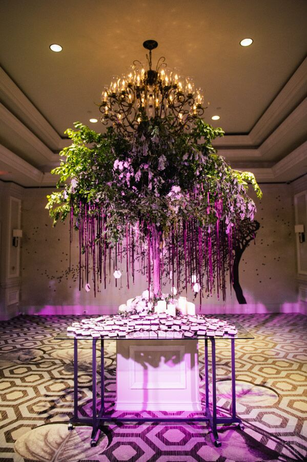 Escort card tags hung from ribbons off a beautiful, tree-like structure at this ballroom reception.