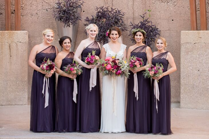 "Jenna's Amsale bridesmaid dresses were long and elegant, matching the look of her gown. ""My dress had beautiful beaded detailing at the top, with delicate lace sleeves, a low back and a cathedral-length veil,"" Jenna says of her Anna Campbell gown. The flowers in her hair matched the bouquets."
