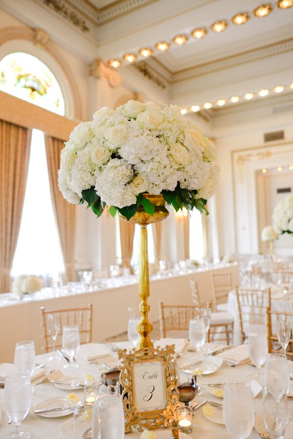 Ivory flowers in gold candelabra centerpiece