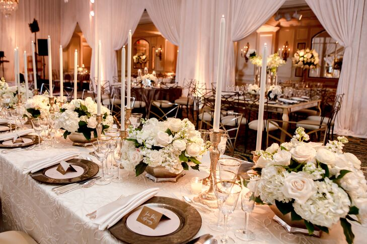 Long tables at the reception were lined with white rose and hydrangea flower arrangements as well as elegant gold candlesticks. The hall was draped with white linens, creating a romantic and intimate effect.