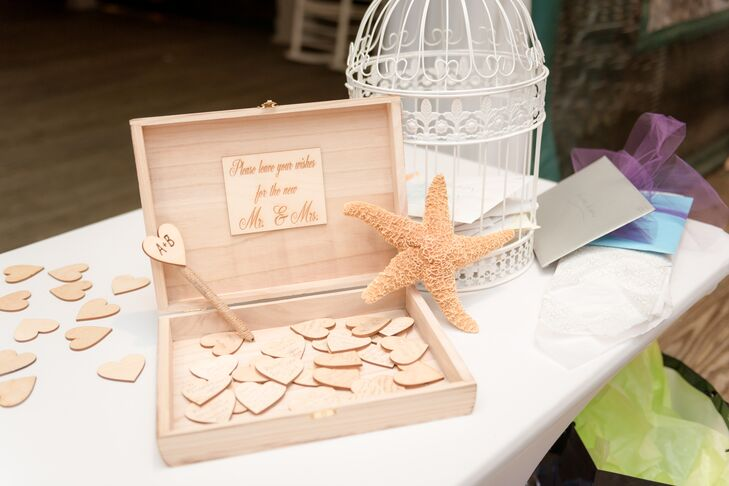 "In lieu of the traditional wedding guest book, Bethany and Ali came up with a different idea. They set out heart-shaped pieces of wood and a wooden chest that read, ""Please leave your wishes for the new Mr. and Mrs."" They placed it on the gift table next to the card holder for guests to sign at some point during the reception."