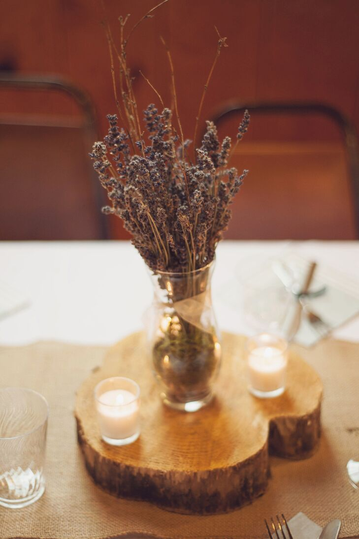 "Dried lavender was arranged inside a glass vase next to white candles, and perched on top of a wooden slab cut from trees on Khara's parent's property by Brad. ""All the wedding decor was handmade, and many tables were decorated differently to add interest and variety,"" the couple says."