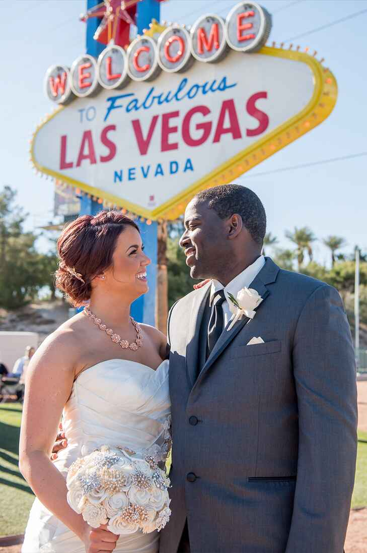 just-married couple standing under the welcome to las vegas sign