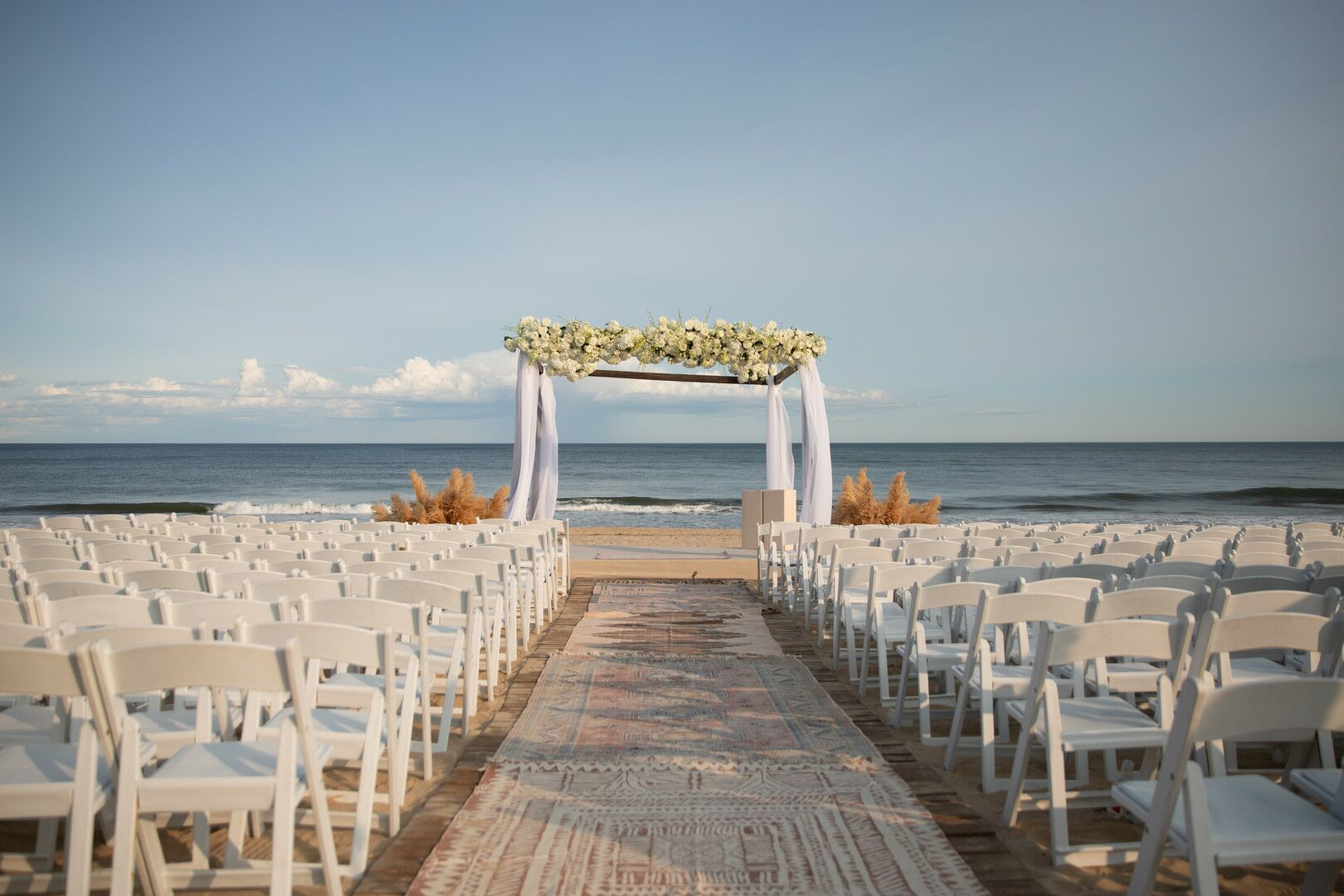 Classic Beach Ceremony With Wedding Arch And White Folding Chairs