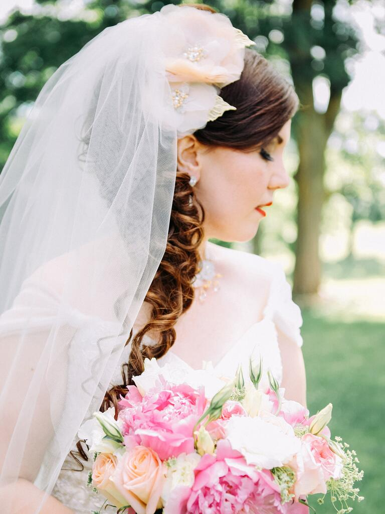Curled wedding hairstyle with a floral hair accessory and veil