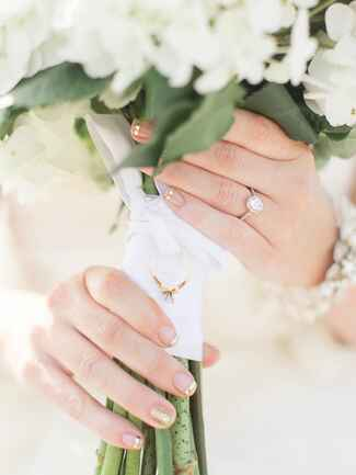 A bride's hands with gold tips holding a white floral bouquet