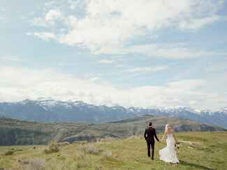 Bride and groom walking with a view of mountaintops in the distance