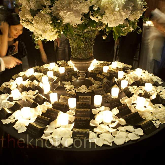 A French wire urn filled with hydrangea, hybrid roses and phlox stood in the center of the escort card display. The cards were arranged in vertical rows and separated with white rose petals and glowing votive candles, creating a warm scene for arriving guests.