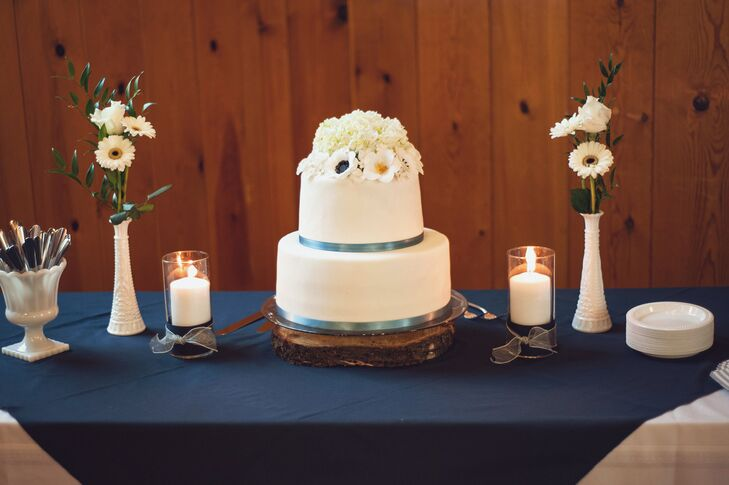 The two-tiered ivory wedding cake was laced at the bottom with blue ribbon and decorated on the top with an assortment of ivory flowers. The cake was covered in white frosting, with one layer of carrot cake, which was Brad's favorite, and the other with chocolate cake and raspberry filling.