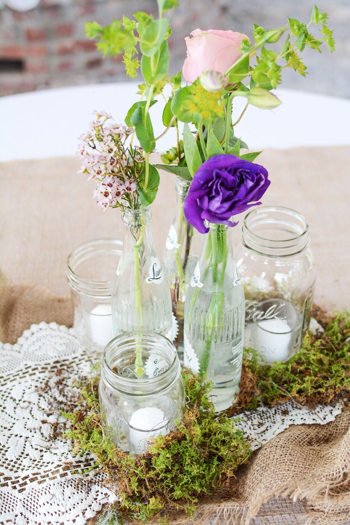 Wildflower centerpieces in glass bottles